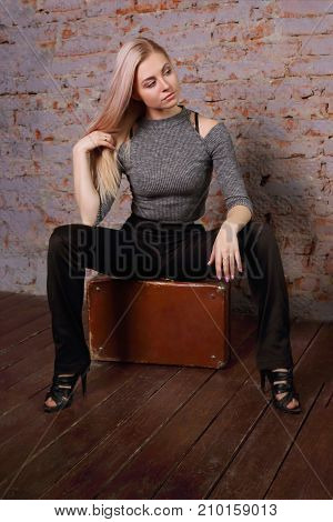 Beautiful young woman in striped blouse posing near brick wall in photo studio sits on suitcase looks away