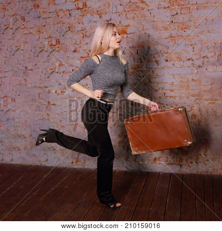 Beautiful young woman in striped blouse posing near brick wall in photo studio runs with suitcase