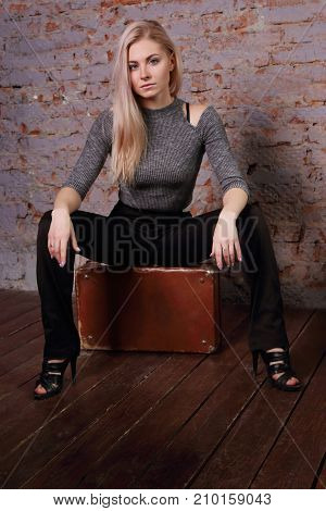 Beautiful young woman in striped blouse posing near brick wall in photo studio is sitting on suitcase
