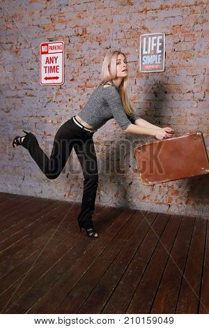 Beautiful young woman in striped blouse posing near brick wall in photo studio runs with suitcase late