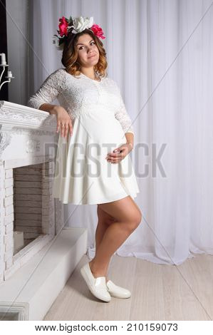 beautiful pregnant woman in white dress and wreath in her hair is standing near fireplace hand lies on belly