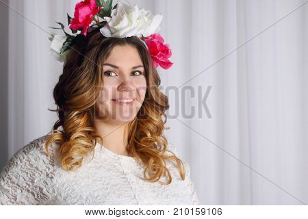 portrait of beautiful woman in white dress and wreath in her hair