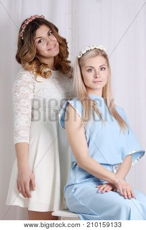 two beautiful girls in dresses with flowers in her hair in studio one is sitting other is standing looks at camera