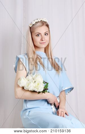 Beautiful young blonde woman with clean skin and flower wreath in her hair near curtain roses greek