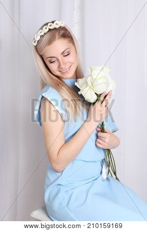 Beautiful young blonde woman with clean skin and flower wreath in her hair on grey background Keep flowers and smile