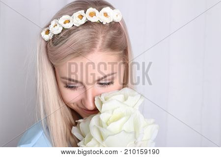 Beautiful young blonde woman with clean skin and flower wreath in her hair holding bouquet white rose confused