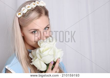 Beautiful young blonde woman with clean skin and flower wreath in her hair smelling bouquet white rose and smile