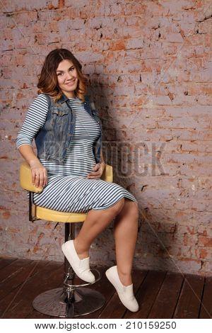 beautiful pregnant woman in striped dress jacket is sitting on bar stool near brick wall in studio