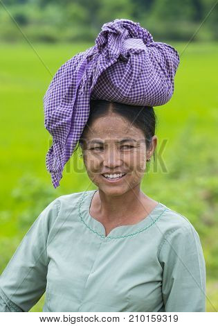 SHAN STATE MYANMAR - SEP 06: Portrait of Burmese farmer working at a rice field in Shan state Myanmar on September 06 2017 Myanmar is the world's sixth largest rice producing country