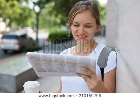 Closeup portrait of smiling young beautiful woman leaning on wall, holding drink and reading newspaper on street. Front view.