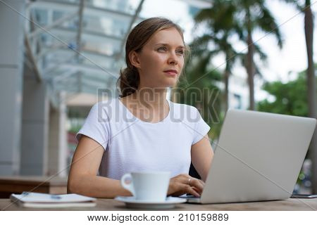 Closeup portrait of serious young beautiful woman working on laptop computer at cafe table outdoors with street view in background