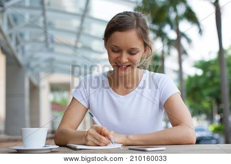Closeup portrait of smiling young beautiful woman working and making notes at cafe table outdoors with street view in background. Front view.