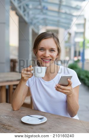 Closeup portrait of smiling young beautiful woman looking at camera, drinking coffee and using smartphone at cafe table outdoors with street view in background. Front view.
