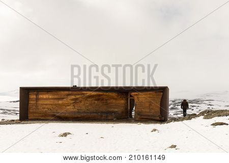 Viewpoint Snohetta in Dovrefjell, Norway, vinter and snow on Tverrfjellet. Man standing next to the building.