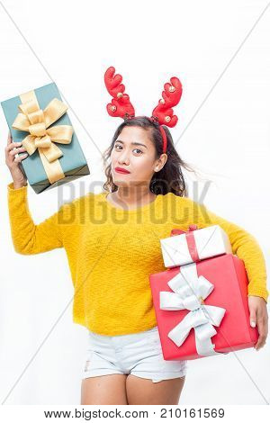 Closeup portrait of content middle-aged woman wearing toy reindeer horns and holding three gift boxes. Isolated front view on white background.