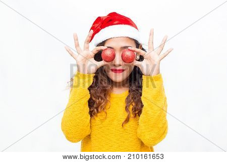 Closeup portrait of playful middle-aged woman wearing Santa Claus hat and holding Christmas balls in front of eyes. Isolated front view on white background.
