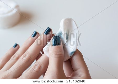Woman removes the nail polish. Hands with dark blue manicure on whote table.