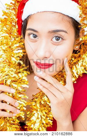 Close-up of face of young Asian woman wearing Santa hat wrapped in tinsel looking at camera and smiling. Christmas and New Year concept