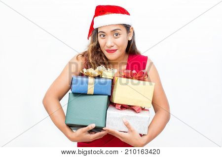 Portrait of happy young Asian woman wearing red dress and Santa hat carrying heap of gift boxes, looking at camera and smiling. Christmas and shopping concept