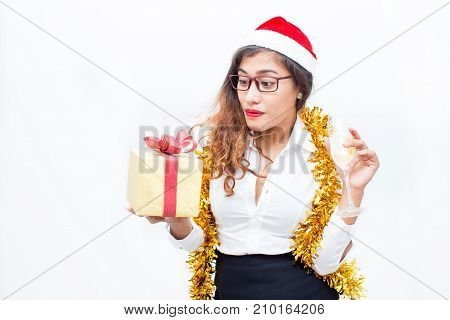 Portrait of surprised young Asian woman wearing eyeglasses and Santa hat Santa hat, glasses and tinsel holding champagne flute and looking at gift box. Christmas and office party concept