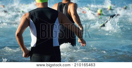 Triathletes running out of the water on triathlon race