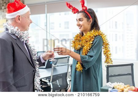 Senior boss in Santa hat passing flute to assistant at office party. Cheerful Indian colleague taking champagne flute enjoying conversation with executive. Christmas party concept