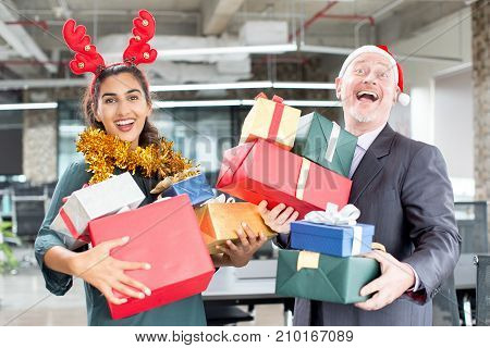 Laughing boss and secretary excited about Christmas looking at camera. Cheerful positive managers holding heap of presents. Christmas in office concept