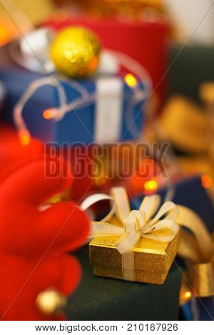 Cute yellow box wrapped in ribbon for Christmas. Close-up of small gift against stack of presents. Gift from Santa concept