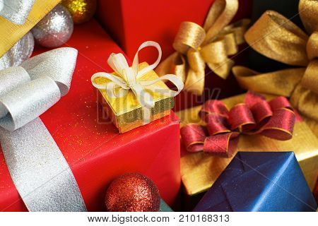 Pretty yellow gift box on big red present. Close-up of Christmas girt wrapped in ribbon for special occasion. Xmas concept