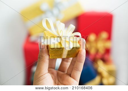 Small Christmas present in petty package for friend. Close-up of female hand holding yellow box wrapped in ribbon. New Year concept