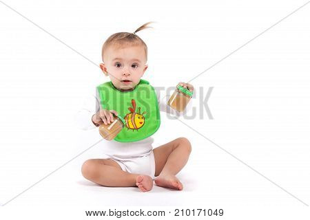 Cute Beautiful Baby Girl In White Shirt And Green Bib Sit And Hold Baby Food