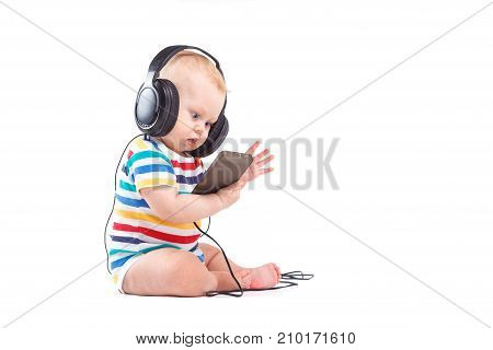 Cute Joyful Baby Boy In Colorful Shirt And Headphones On Head Hold Player