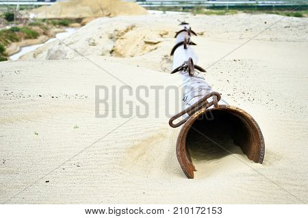 The dry pipe of the dredger lies on the sand in the sand quarry.