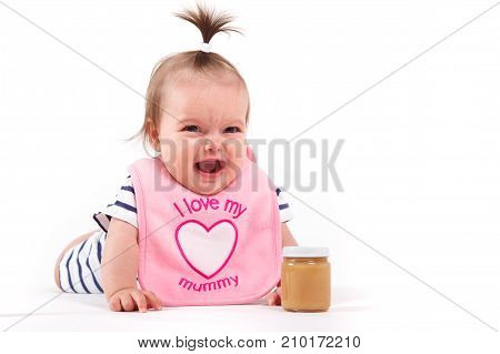 Cute Cheerful Little Girl In Pink  Bib With Baby Food