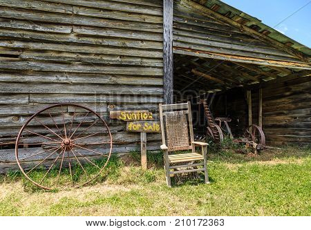 A sign Sunflower for Sale by an old Chair and old rustic barn and rusty wheel