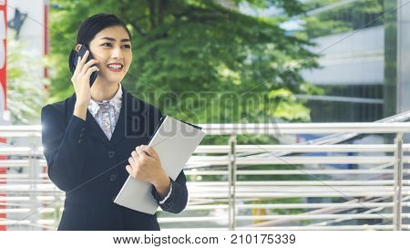 Asian business woman uses and talks on mobile phone with the paper file work on her hand at outdoor public space