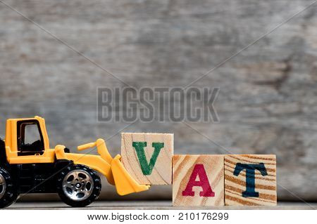 Yellow plastic bulldozer hold letter V to complete word VAT (Abbreviation of Value Added Tax) on wood background