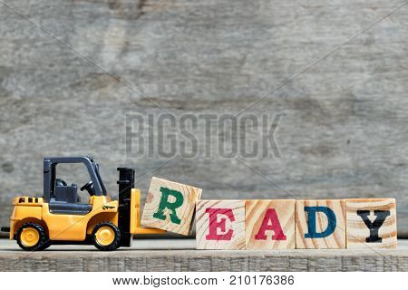 Yellow plastic forklift hold letter R to complete word ready on wood background
