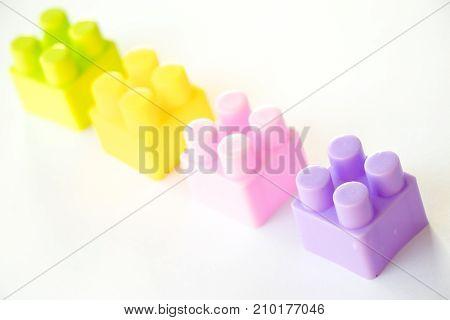 Multi color square plastic toy block on white background
