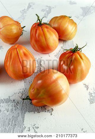 Whole organic tomatoes Coeur De Boeuf. Beefsteak tomato on white rustic table.
