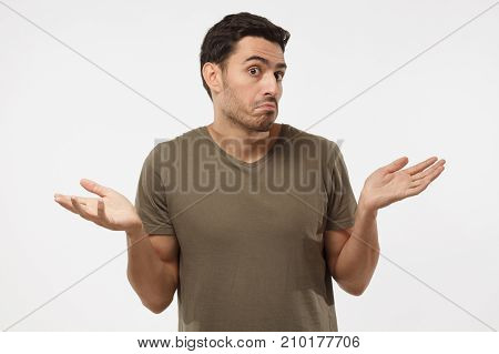 I Don't Know. Young Man Isolated On Grey Background Being At A Loss, Showing Helpless Gesture With A