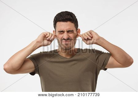 Stressed Frustrated Young Man Plugging His Ears With Fingers And Keeping Eyes Closed While Having He