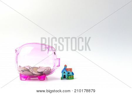 Clear pink Piggy bank and house model on white for saving money finance and banking concept.
