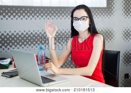 Pretty, Young Businesslady In Red Dress, Gas Mask And Glasses Sit At The Table And Work