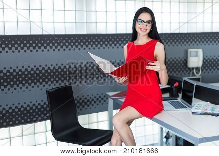 Attractive Businesslady In Red Dress And Glasses Sit On The Table And Hold Paper Folder