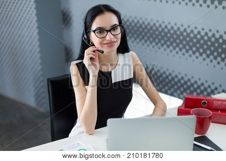 Young Attractive Businesslady In Black Dress And Glasses Sit At The Table And Work With Laptop
