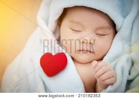 Family love relationship concept : red heart shaped put on sleep cute Asian baby. Lovely newborn Asia infant model female in her first year