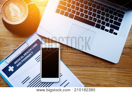 medical health care insurance online concept : medical health care policy document on clipboard with laptop and blank screen mobile phone on table