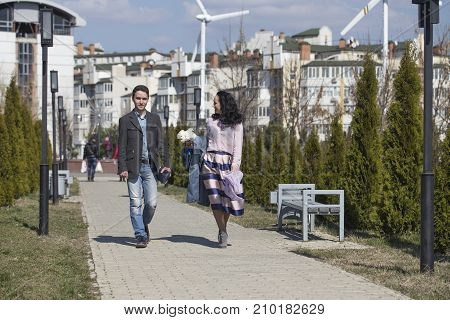 Mother and son are together. Couple strolling in the park near a fountain.