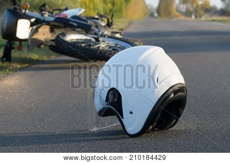 Photo of helmet and motorcycle on road the concept of road accidents